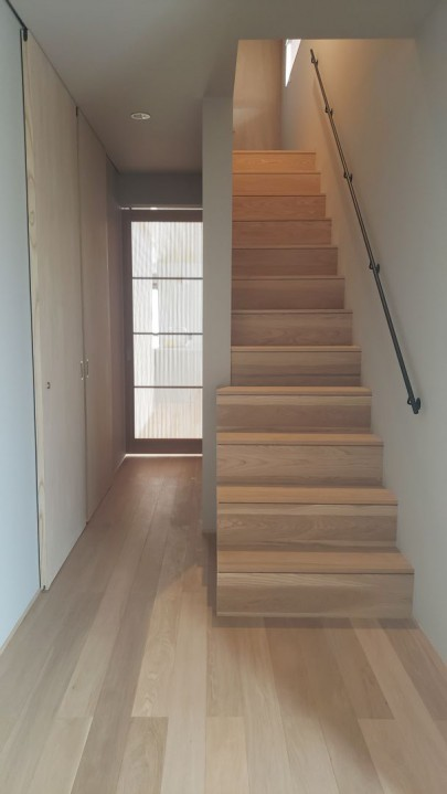 エントランスからは奥の千本格子を用いた建具と2階窓からの自然光で より一層落ち着きのある空間になっています。